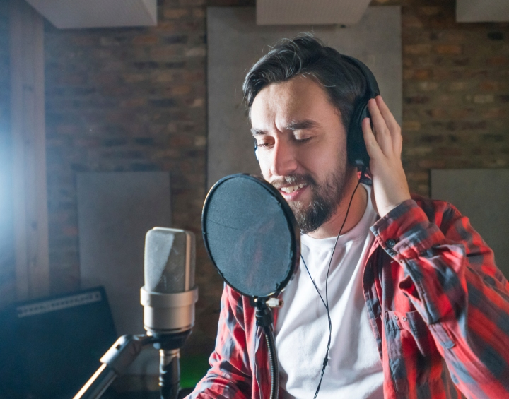 Singer singing on a microphone in a recording studio - music industry concepts